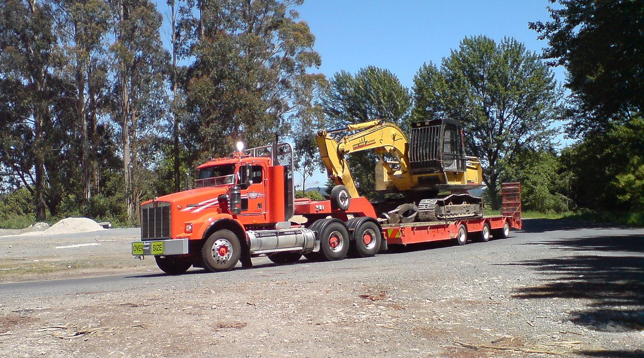 A gooseneck lowboy trailer with an oversized load