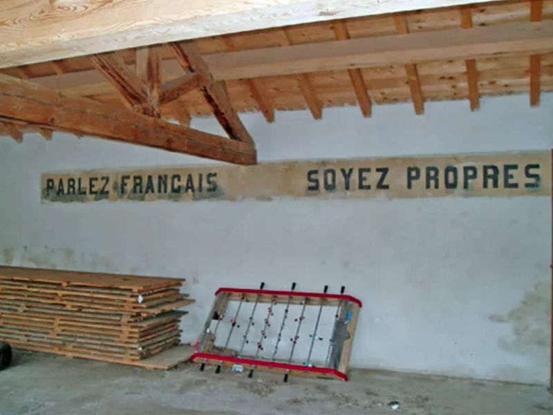 """Speak French, Be Clean"" written across the wall of a Southern French school"