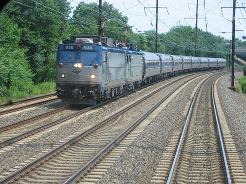 An electric Amtrak train with two AEM-7 locomotives running through New Jersey on the Northeast Corridor. The catenary system is clearly visible