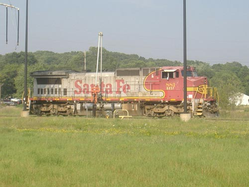 "Santa Fe Dash 8 #881 is sitting at CN's Battle Creek fueling depot, displaying the modern interpretation of the company's classic red and silver ""warbonnet"" livery"