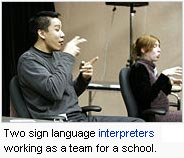 Two sign language interpreters working as a team for a school.